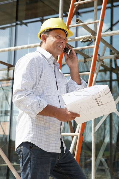 Stock photo: Architect With Plans Outside New Home Talking On Mobile Phone