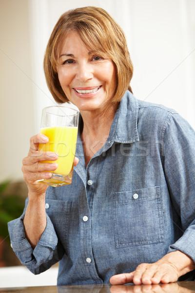 Mid age woman drinking orange juice Stock photo © monkey_business