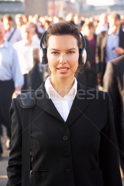 Female commuter in crowd wearing headphones Stock photo © monkey_business