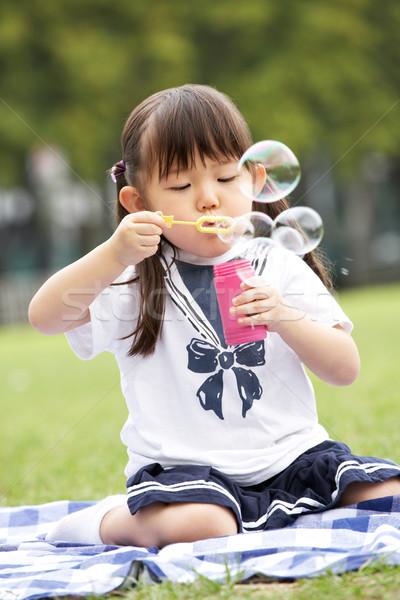Fiatal kínai lány park buborékfújás boldog Stock fotó © monkey_business