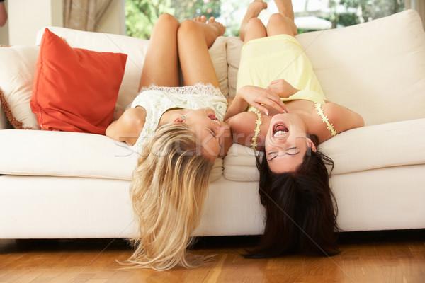 Twee vrouwelijke vrienden ondersteboven sofa vrouwen Stockfoto © monkey_business
