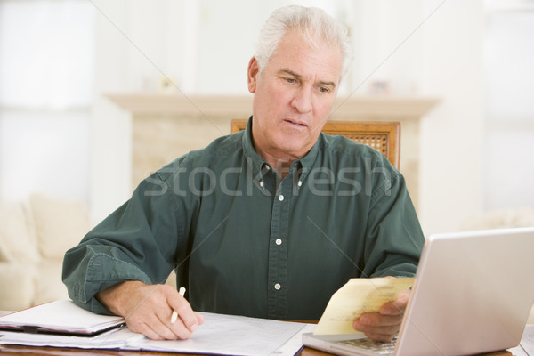 Man in dining room with laptop and paperwork looking unhappy Stock photo © monkey_business