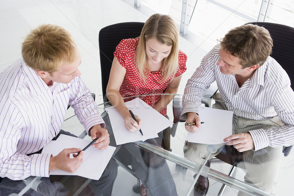 Three businesspeople in boardroom with paperwork Stock photo © monkey_business