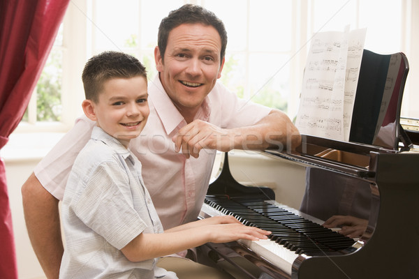 Man and young boy playing piano and smiling Stock photo © monkey_business