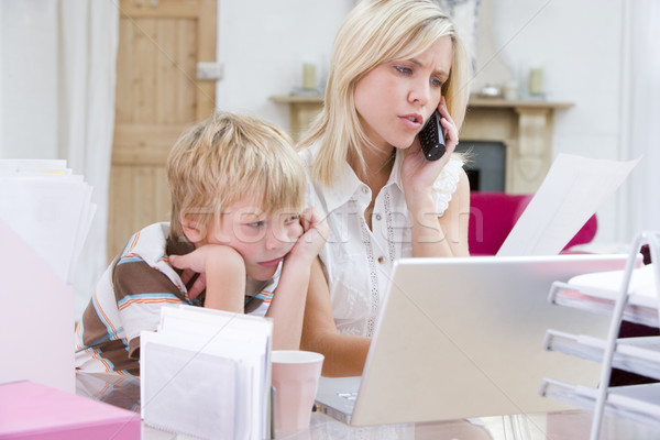 Woman using telephone in home office with laptop while young boy Stock photo © monkey_business