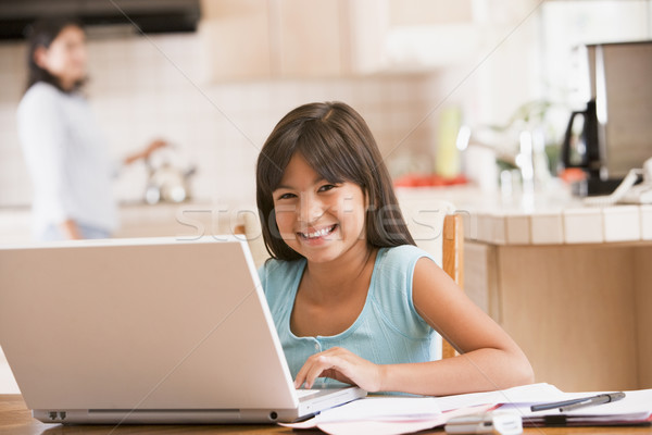 Young girl in kitchen with laptop and paperwork smiling with wom Stock photo © monkey_business