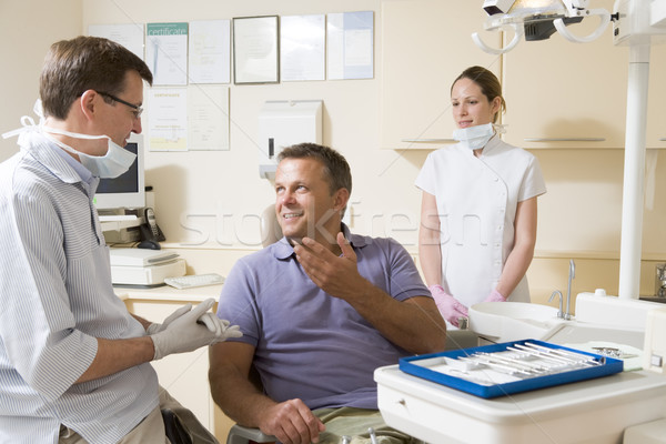 Dentist and assistant in exam room with man in chair smiling Stock photo © monkey_business