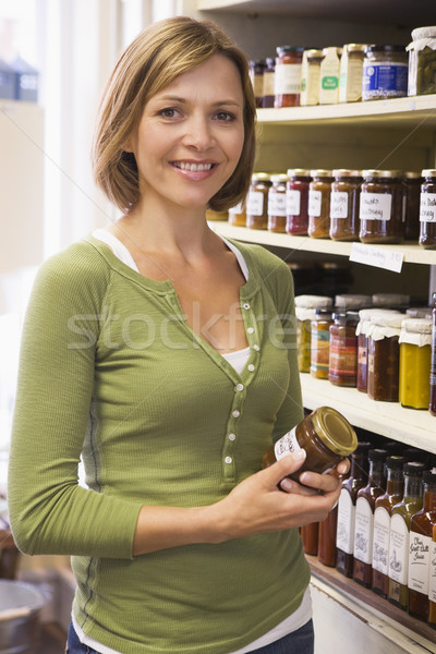 Woman in market looking at preserves smiling Stock photo © monkey_business