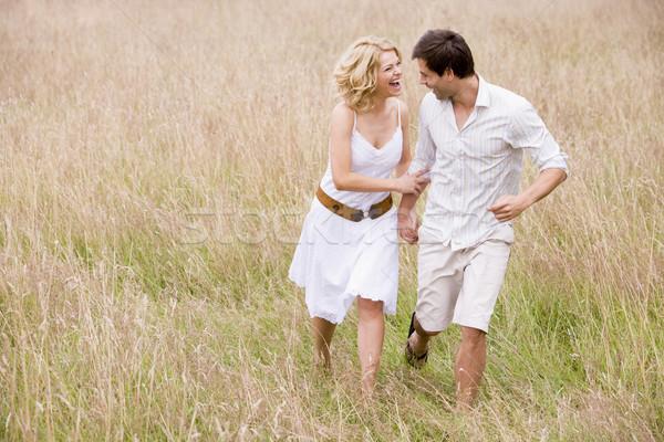 Stockfoto: Paar · lopen · buitenshuis · holding · handen · glimlachend · gras
