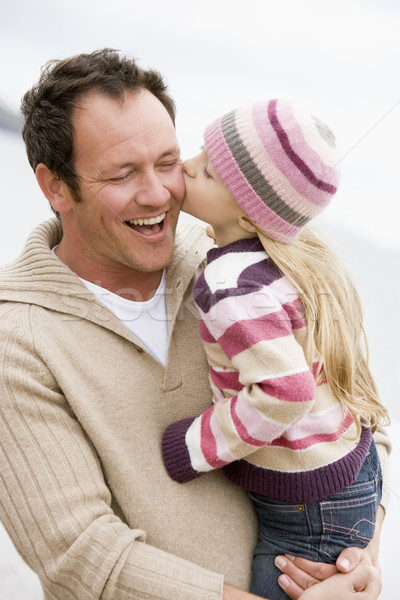 Father holding daughter kissing him at beach smiling Stock photo © monkey_business