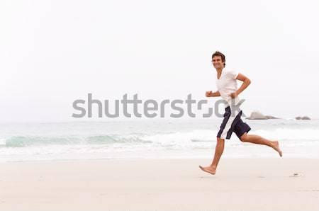 Młody człowiek uruchomiony zimą plaży człowiek morza Zdjęcia stock © monkey_business