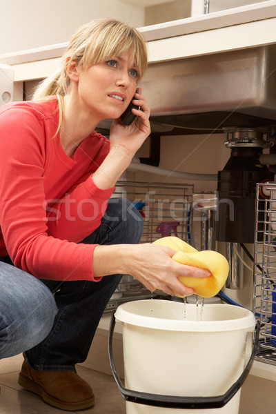 Woman Mopping Up Leaking Sink On Phone To Plumber Stock photo © monkey_business