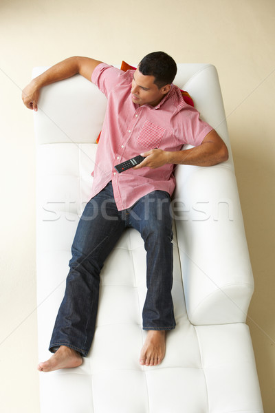 Overhead View Of Man Relaxing On Sofa Watching Television Stock photo © monkey_business