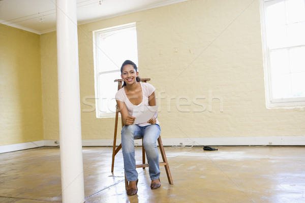Woman sitting on ladder in empty space holding paper smiling Stock photo © monkey_business
