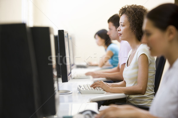 Quatre personnes séance salle informatique tapant femme bureau Photo stock © monkey_business