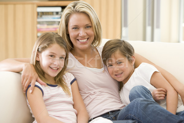 Stock photo: Woman and two young children in living room smiling