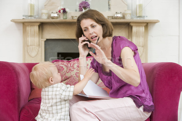 Mother using telephone in living room with baby frowning Stock photo © monkey_business