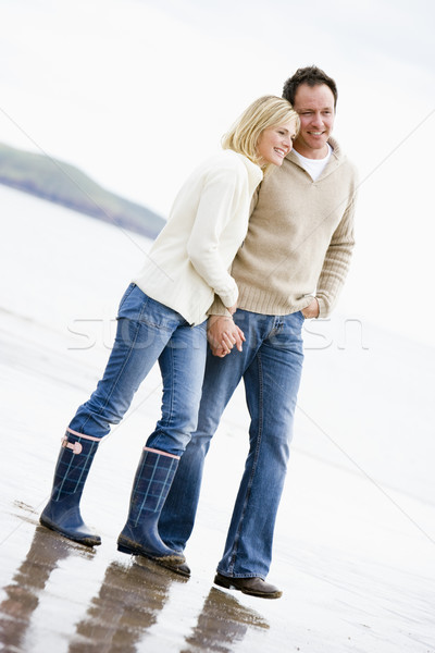 Stock photo: Couple walking on beach holding hands smiling