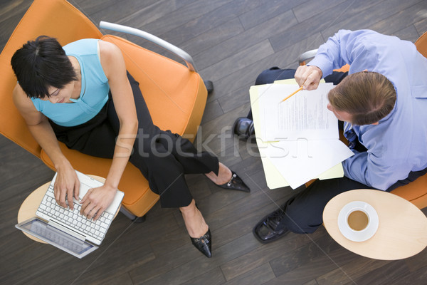 Two businesspeople sitting indoors with coffee laptop and folder Stock photo © monkey_business
