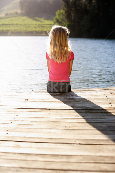 Young girl sitting by lake Stock photo © monkey_business