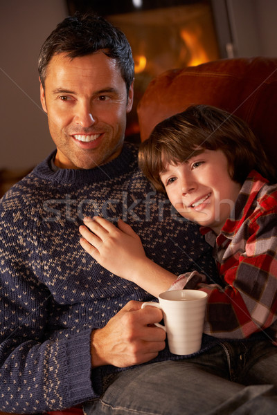 Father And Son Relaxing With Hot Drink Watching TV By Cosy Log F Stock photo © monkey_business