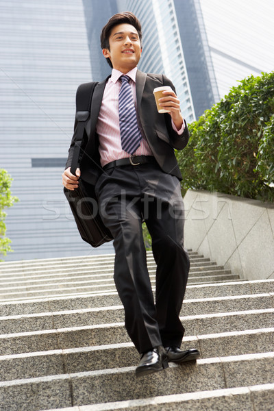 Stock photo: Chinese Businessman Rushing Down Steps Carrying Bag And Takeaway