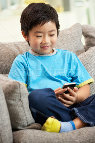 Young Chinese Boy Using Mobile Phone On Sofa At Home Stock photo © monkey_business