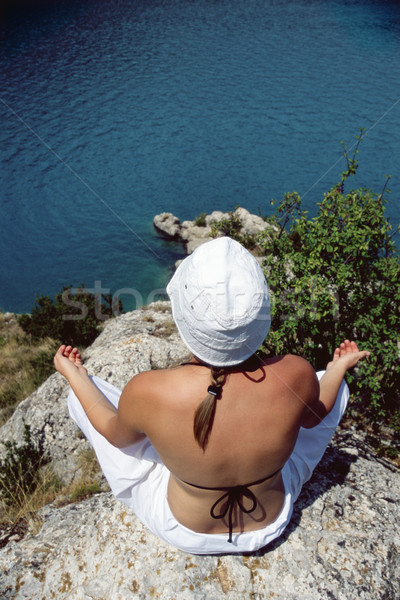 Young woman meditating on rocks at water's edge Stock photo © monkey_business