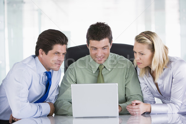 Three businesspeople in a boardroom looking at laptop Stock photo © monkey_business