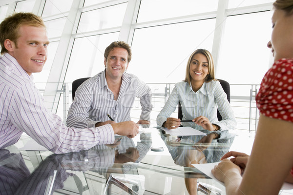 Four businesspeople in a boardroom with paperwork smiling Stock photo © monkey_business