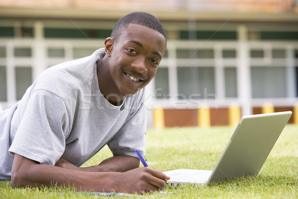 College student using laptop on campus lawn Stock photo © monkey_business