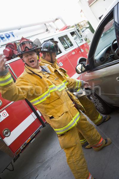 Firefighters cutting open a car to help an injured person Stock photo © monkey_business