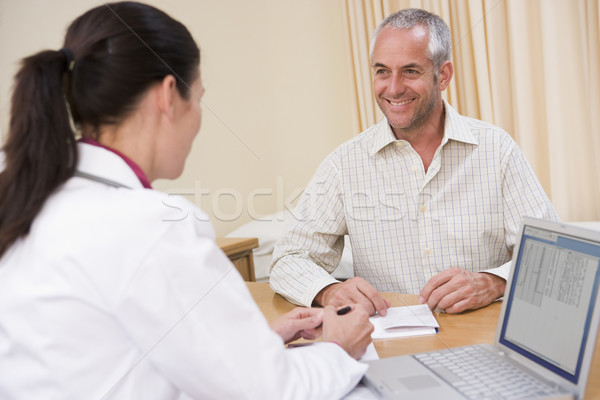 Doctor with laptop and man in doctor's office smiling Stock photo © monkey_business