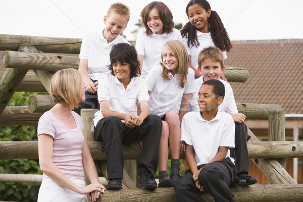 School children sitting on benches outside with their teacher Stock photo © monkey_business