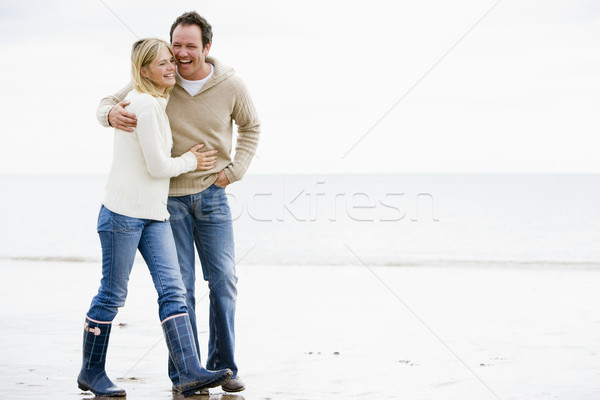 Couple walking on beach arm in arm smiling Stock photo © monkey_business