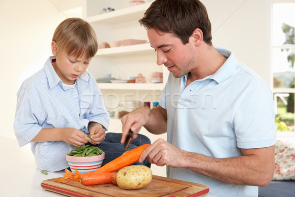 Happy young man with boy peeling vegetables in kitchen Stock photo © monkey_business