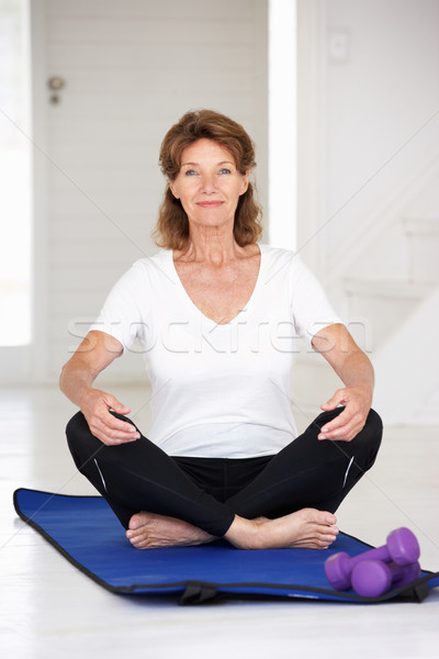Senior woman sitting in lotus position Stock photo © monkey_business