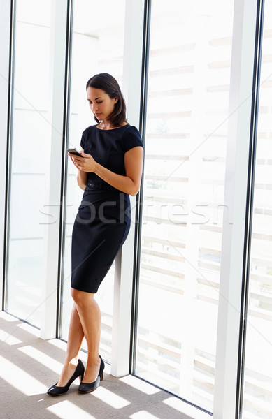 Businesswoman Using Mobile Phone In Office Stock photo © monkey_business