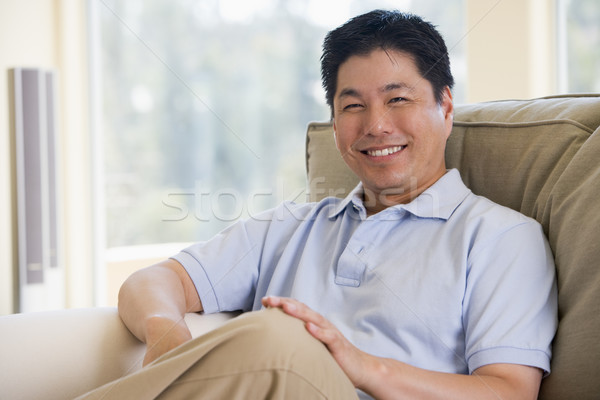 Man sitting in living room smiling Stock photo © monkey_business