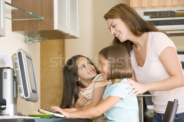 Woman and two young girls in kitchen with computer smiling Stock photo © monkey_business