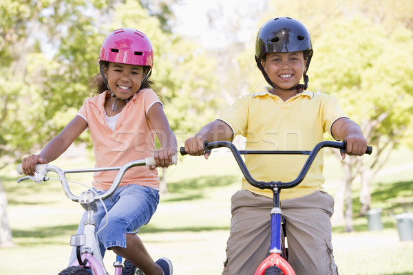 Brother and sister outdoors on bicycles smiling Stock photo © monkey_business