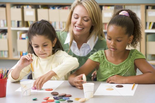 Kindergarten teacher sitting with students in art class,  Stock photo © monkey_business