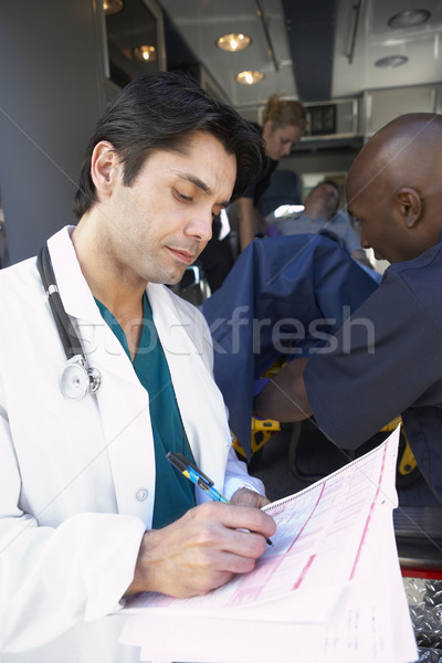 Doctor taking notes as paramedics unload patient Stock photo © monkey_business