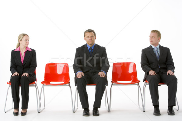 Stock photo: Three Business People Sitting On Red Plastic Seats