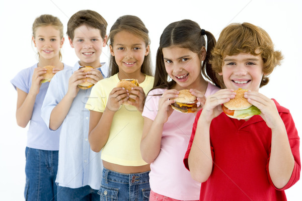 Row of five young friends eating hamburgers Stock photo © monkey_business