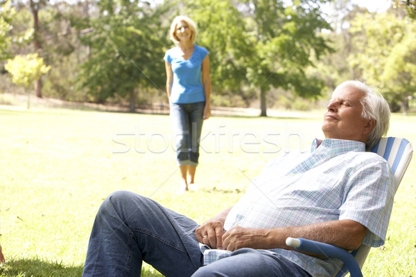 Senior Man Relaxing In Park With Wife In Background Stock photo © monkey_business