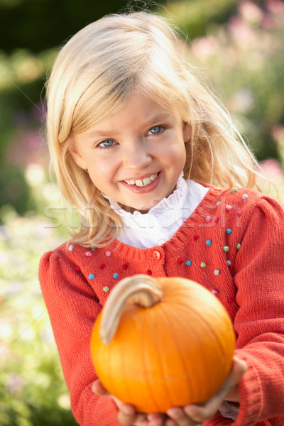 Young girl posing with pumpkin in garden Stock photo © monkey_business