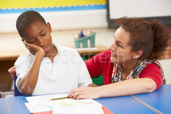 Unhappy Schoolboy Studying In Classroom With Teacher Stock photo © monkey_business