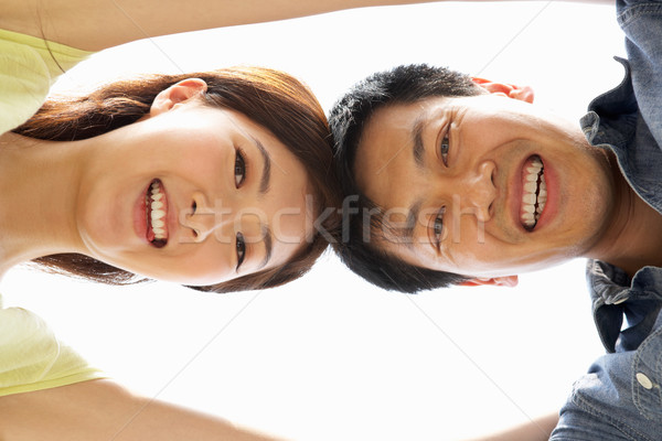 Stock photo: Young Chinese Couple Looking Down Into CameraTogether