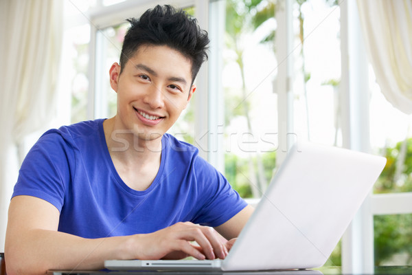 Young Chinese Man Sitting At Desk Using Laptop At Home Stock photo © monkey_business